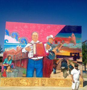 Jesus Alvarado in front of a mural he painted.